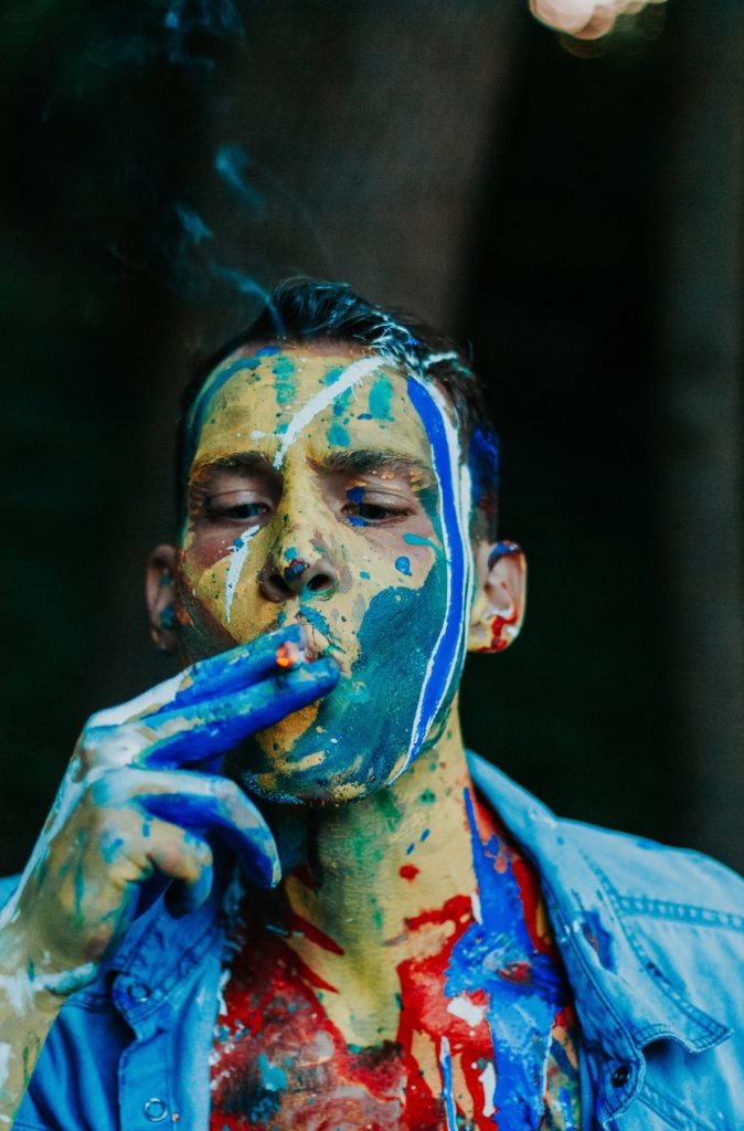 A man smoking a joint with paint on his face